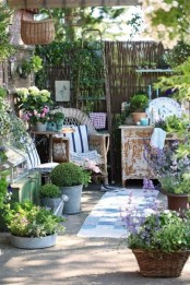 a shabby chic and rustic spring terrace with wicker chairs, shabby cabinets, baskets and buckets with greenery and blooms and decorative plates