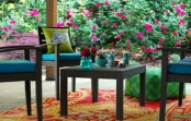 a bright spring terrace with dark furniture, colorful upholstery, bright pillows and rugs and blooms around