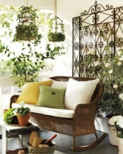 a refined vintage spring terrace with a forged screen, greenery and blooms, a wicker bench and bold pillows, greenery cages and potted greenery