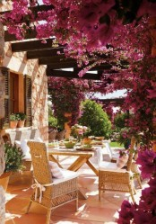 a French chic terrace wiht bougainvillea covering it completely, a wooden table, wicker chairs and neutral textiles
