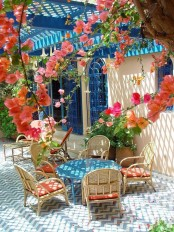 a colorful Mediterranean terrace with blue tiles, wicker chairs, a blue table and bright blooms all around