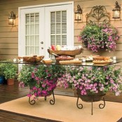 a spring patio with a creative table placed on blooming planters, with a blooming planter on the wall, some potted greenery and a glass table