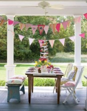 a boho spring terrace with a wooden table, chairs and a bench, colorful linens, pillows and banners over the space plus blooms