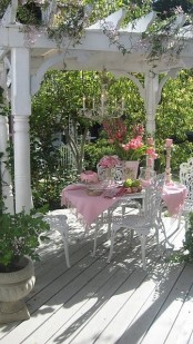 a refined vintage spring terrace with luxurious white furniture, some blooms and greenery around and pink linens is all chic