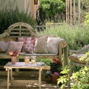 a refined shabby chic spring terrace with shabby chic furniture, potted plants and blooms and floral pillows and textiles and greenery around
