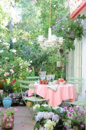 a bloom-filled spring terrace with potted greenery and flowers all around, with a dining set, a chandelier and some fresh fruit
