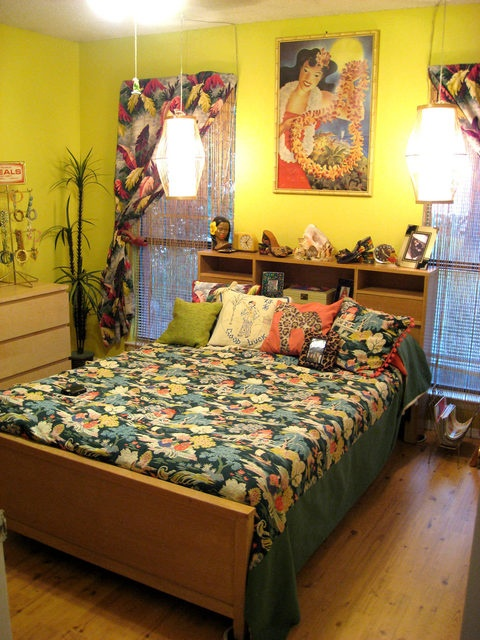 neon yellow walls, a bright artwork and tropical print textiles make this bedroom feel tropical and colorful