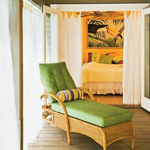 bright bedding and printed pillows, a statement artwork, a wicker lounger with green upholstery for a tropical feel