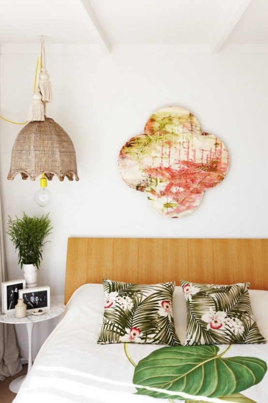 a contemporary tropical bedroom with bright printed pillows, a bold artwork and a wicker lampshade over the bed