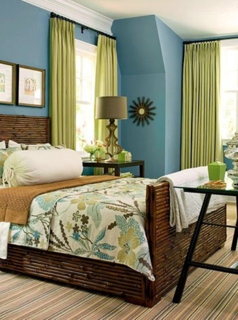 a dark stained bamboo wooden bed, bright green touches, a striped rug and blue walls