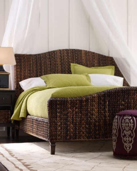 a dark wicker bed with an airy sheer canopy, dark stained furniture and a purple ottoman