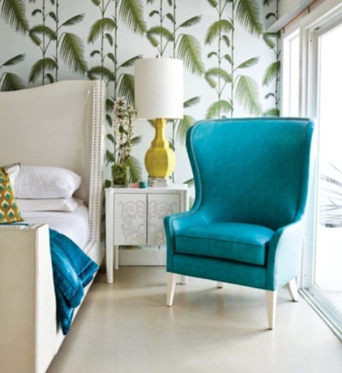 tropical print wallpaper, a bright turquoise chair and a neutral upholstered bed for a glam tropical space