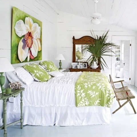a whitewashed bedroom with bright pistachio green touches, palm leaves, a shabby chic bench and a statement artwork