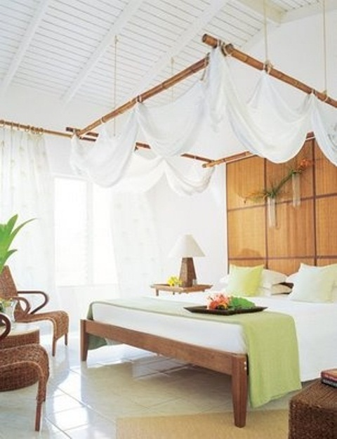 a tropical bedroom with a canopy hanging over the bed, wicker chairs, touches of green for refreshing the space