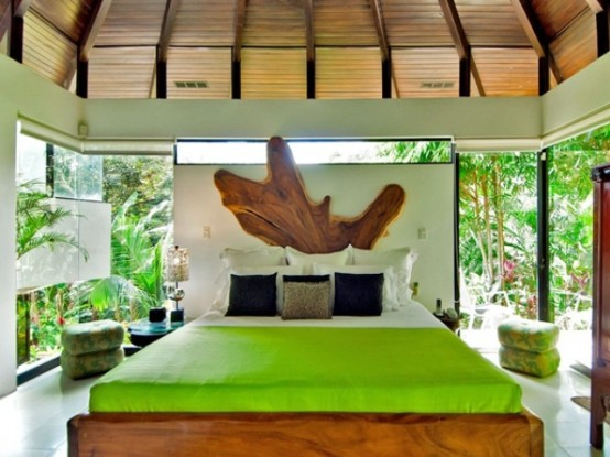 a live edge wooden bed, neon green touches, a live edge headboard and glazed walls that feature tropical views