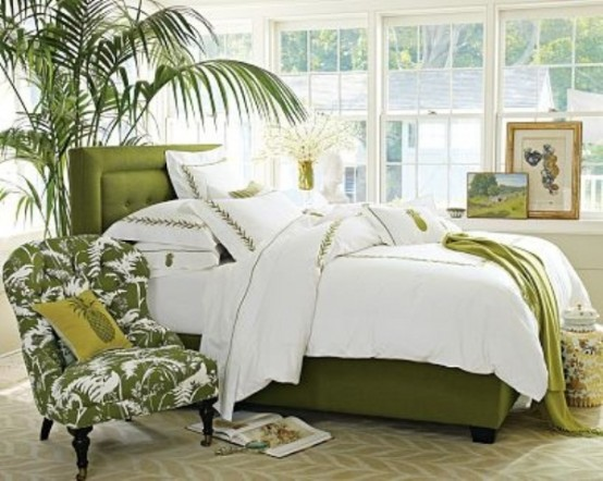 bright green touches, a potted palm tree, a grene printed chair make the bedroom feel tropical