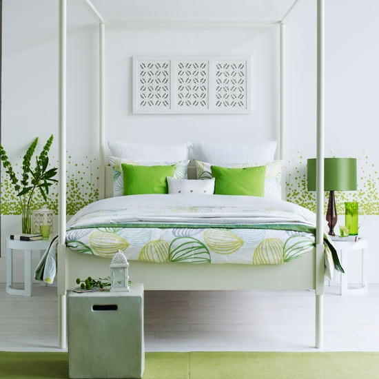 a bright white and green bedroom with patterns on the wall and bedding, a green lamp and pillows