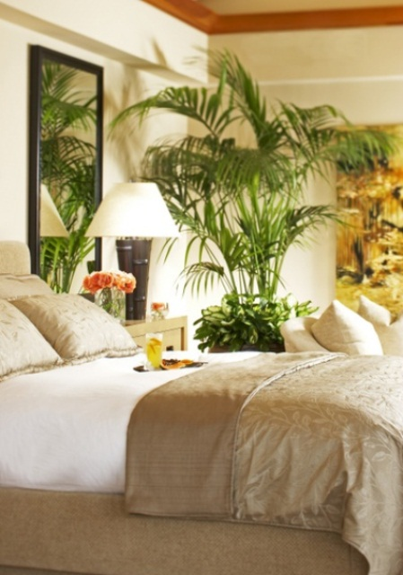 a tropical feel is achieved with potted plants and bamboo base lamps in a neutral bedroom