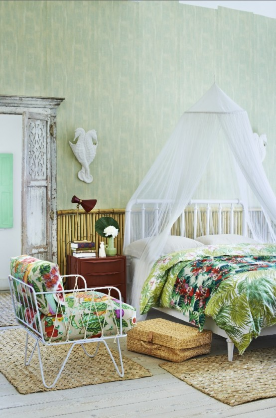 green printed wallpaper, bright tropical print textiles, wicker rugs and a bamboo wall make the bedroom feel tropical