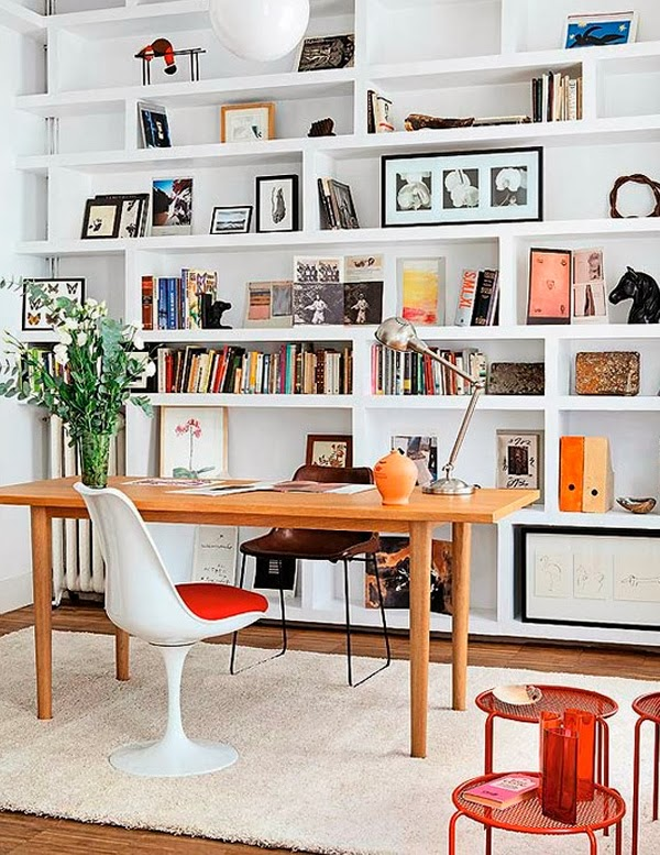 a welcoming and light filled home office with a whole wall of built in shelves and some furniture is a cool space to work