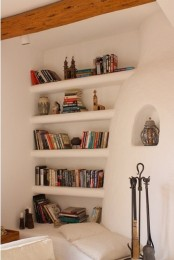 a concrete white wall with built-in shelves where you can place books and other stuff you want