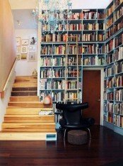 an entryway library covered with built-in bookshelves, with a vintage chandelier and a black chair is amazing to make use of your space