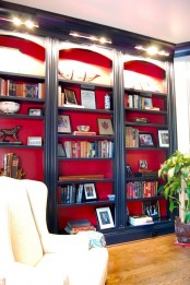 stylish navy built-in bookshelves with red backing and additional lights over the shelves are amazing for a refined space