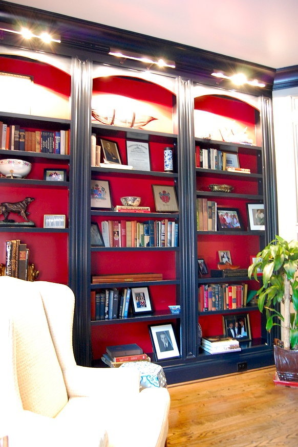 stylish navy built in bookshelves with red backing and additional lights over the shelves are amazing for a refined space