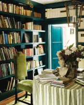 a refined home library with blue built-in bookshelves taking all the walls is a very stylish and cool idea