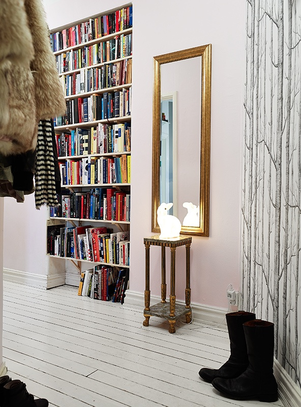 an entryway with lots of built in bookshelves that allow comfortable storage and doesn't steal space from other rooms
