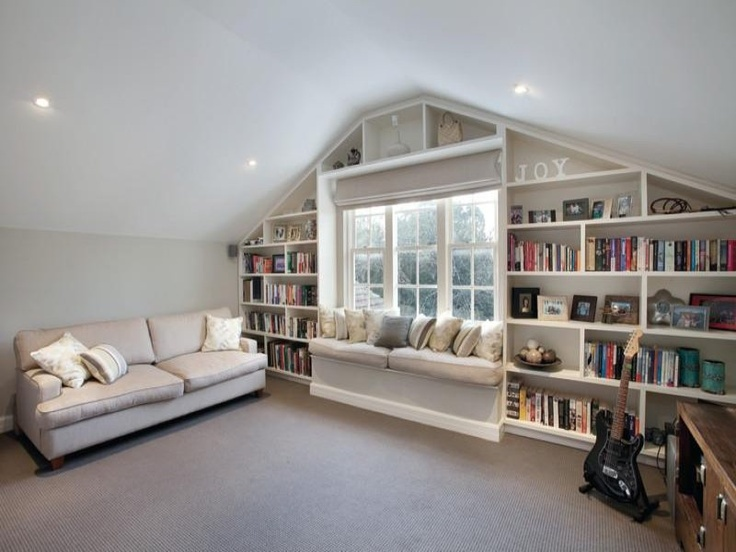 a neutral attic room with built in bookshelves around the window   it's a nice way to store things and save some space