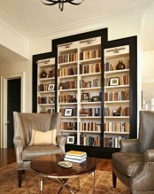 a refined living room with a whole cluster of built-in bookshelves framed in black is a very elegant and stylish piece