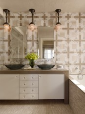 a neutral modern bathroom with a built-in vanity, mismatching tiles, two tinks and mirrors and vintage pendant lamps