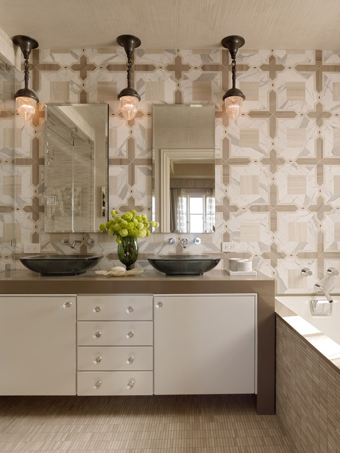 a neutral modern bathroom with a built in vanity, mismatching tiles, two tinks and mirrors and vintage pendant lamps