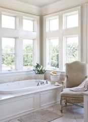 a neutral refined bathroom with a tub clad with panels, a refined vintage chair and  some blooms is a very beautiful and peaceful idea