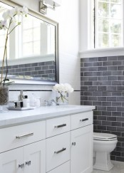 a serene neutral bathroom with grey and white tiles, a white vanity, a large mirror and white blooms for a refined touch