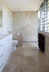 a tan-colored stone tile bathroom with a white vanity and white appliances plus a glazed wall