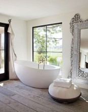 a refined eclectic bathroom with an oval bathtub, an oversized mirror in an ornated frame, a Moroccan ottoman and neutral curtains