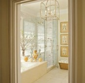 a neutral bathroom with a built-in tub clad with marble, a shower space, a gallery wall and a vintage chandelier