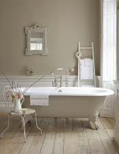 a neutral vintage bathroom with grey walls and white panels, a creamy bathtub, a ladder, a mirror in an ornated frame and a vintage chair