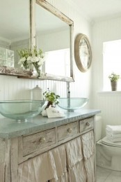 a neutral shabby chic bathroom with a vanity, glass sinks, a double mirror and white beadboard walls