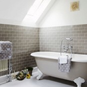 a lovely neutral bathroom with grey subway tiles, a grey clawfoot bathtub and polka dot towels is a cozy and refined space