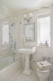 a refined neutral modern bathroom clad with various types of tiles, a free-standing sink and white appliances plus a mirror and a sconce over the mirror