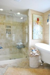 a tan-colored bathroom clad with tiles, with neutral wallpaper, a vintage bathtub and a shower space plus a bold artwork