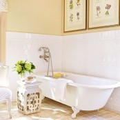 a cozy vintage bathroom with a tile backsplash, a vintage poster gallery wall, a clawfoot tub and a carved side table