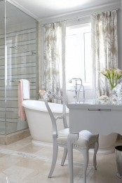 a refined neutral bathroom with tan tiles, stripes in the shower space, white furniture and a vanity plus printed floral curtains