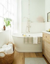 a neutral farmhouse bathroom with beadboard panels, a wooden vanity, a free-standing tub and a basket with towels