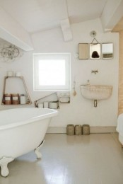 a neutral and industrial vintage bathroom with a clawfoot tub, open shelves, mirrors and a wall-mounted sink