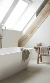 a neutral minimalist attic bathroom with rough wooden beams and a rough wooden bench, neutral towels and a lovely bathtub is amazing