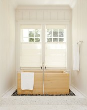 a neutral bathroom with a wood ofuro tub by the windows with shades placed into pebbles